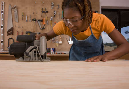 woodcutting: African American woman cutting wood LANG_EVOIMAGES