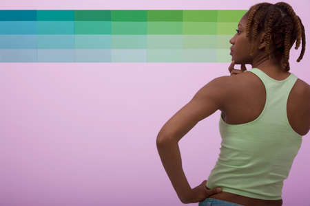 African American woman looking at paint swatches Stock Photo