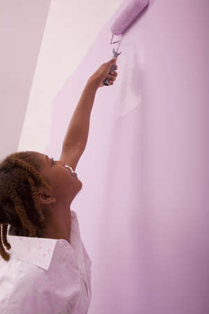 mischeif: African American woman painting with roller