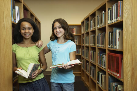 gaiety: Multi-ethnic girls holding library books LANG_EVOIMAGES