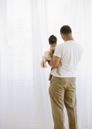 three people only: African American father holding baby