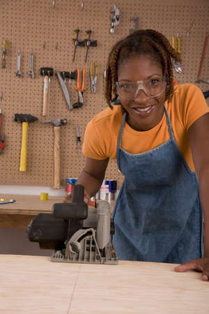 African American woman cutting wood Stock Photo