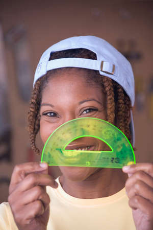 genetically modified crops: African American woman with protractor in front of face