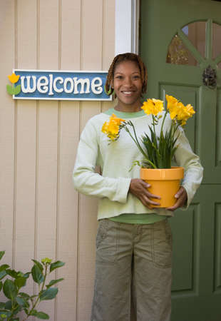 milepost: African American woman holding potted plant