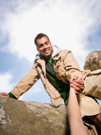 islander: Pacific Islander man helping person climb LANG_EVOIMAGES