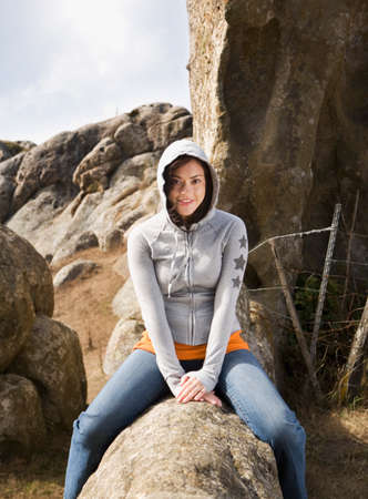 rock formation: Hispanic woman sitting on rock formation