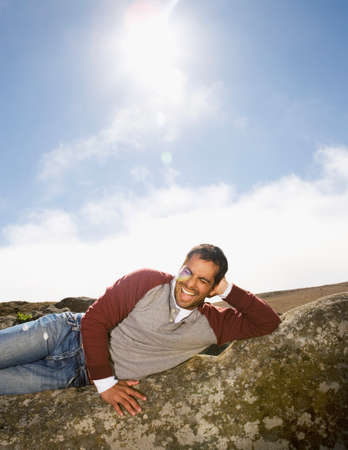 adventuresome: Pacific Islander man laying on rock formation