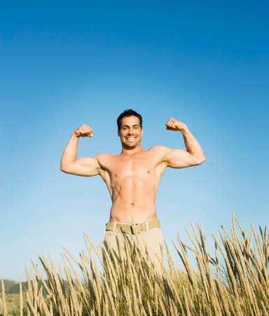 devilment: Pacific Islander man flexing in field LANG_EVOIMAGES