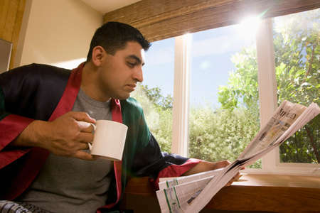 light hearted: Hispanic man reading newspaper