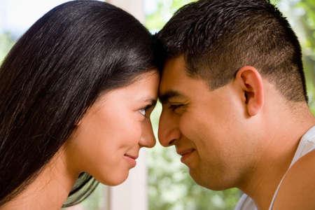 adoring: Multi-ethnic couple touching foreheads