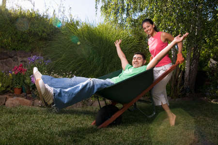 davenport: Mixed Race woman pushing boyfriend in wheelbarrow LANG_EVOIMAGES