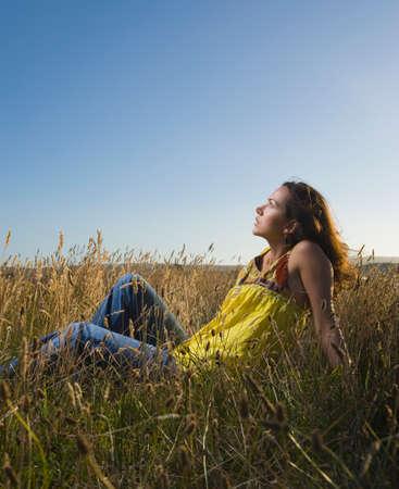 spectating: Hispanic woman sitting in field