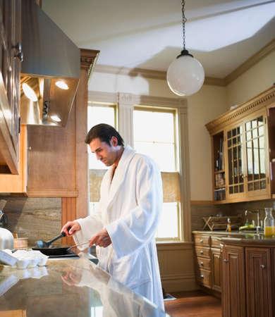 squatter: Hispanic man cooking in bathrobe LANG_EVOIMAGES