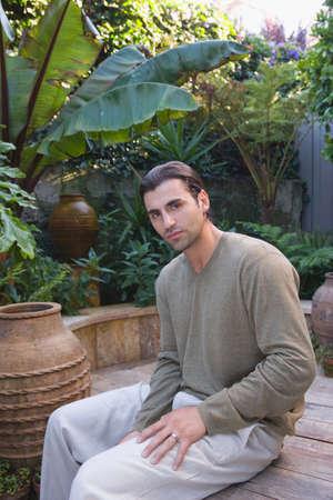 oriental bathrobe: Hispanic man sitting in garden LANG_EVOIMAGES