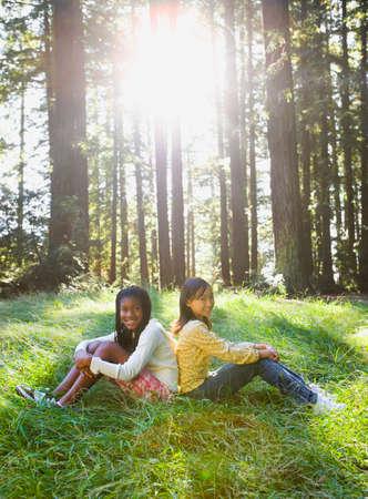 Multi-ethnic girls sitting in woods Stock Photo