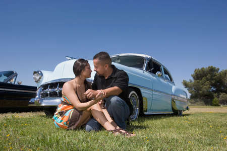 classics: Hispanic couple in front of low rider car