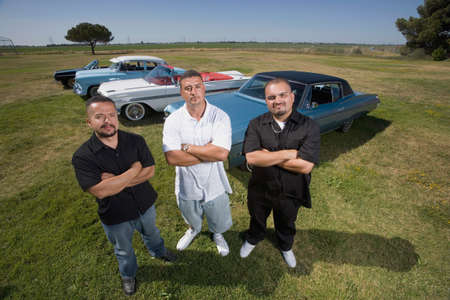 classics: Hispanic men in front of low rider cars LANG_EVOIMAGES