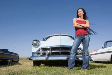 awkwardness: Mixed Race woman in front of low rider car