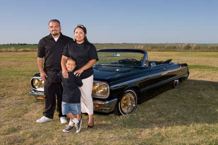 wearying: Hispanic family in front of low rider car