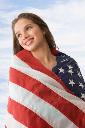 teenaged girl: Hispanic teenaged girl wrapped in American flag LANG_EVOIMAGES