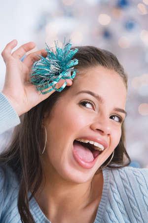 teenaged girl: Hispanic teenaged girl holding bow in hair