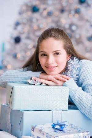 teenaged girl: Hispanic teenaged girl leaning on Christmas gifts LANG_EVOIMAGES