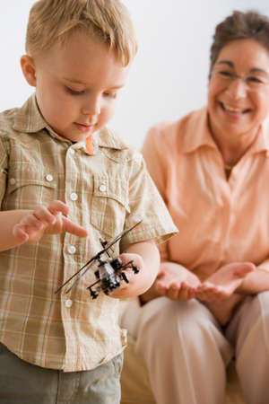 playing on divan: Boy playing with toy helicopter