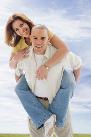 bestowing: African American man giving girlfriend piggyback ride
