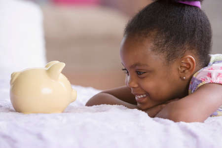 one child only: African American girl looking at piggybank