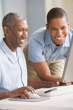 grampa: African American father and adult son looking at computer