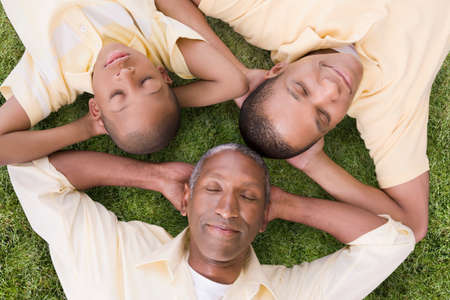 grampa: African American grandfather, father and son laying in grass