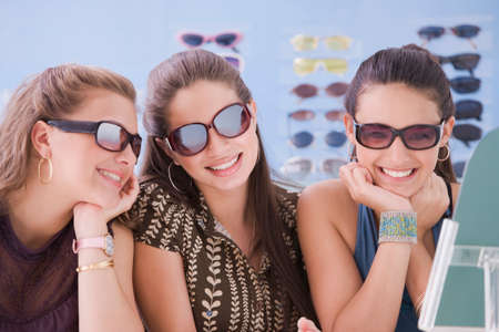 teenaged girls: Multi-ethnic teenaged girls trying on sunglasses LANG_EVOIMAGES