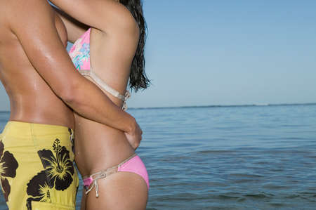 bathing suits: Multi-ethnic couple in bathing suits hugging LANG_EVOIMAGES