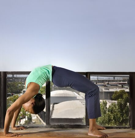 practicing: African woman practicing yoga LANG_EVOIMAGES