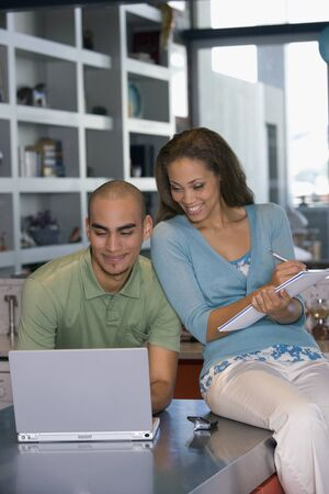 telecommuter: African American couple looking at laptop LANG_EVOIMAGES