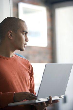 snoozing: African American man holding laptop