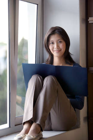 acknowledging: Asian businesswoman reading in window