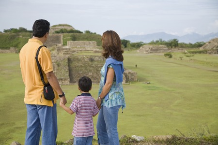 Hispanic family looking at ruins, Oaxaca, Mexico