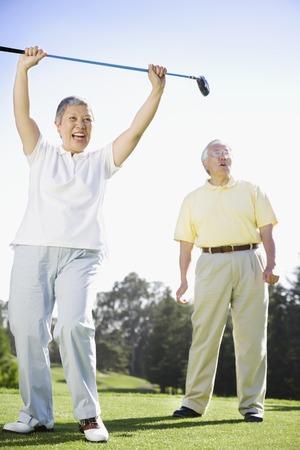 上級アジアの女性のゴルフ コースで応援
