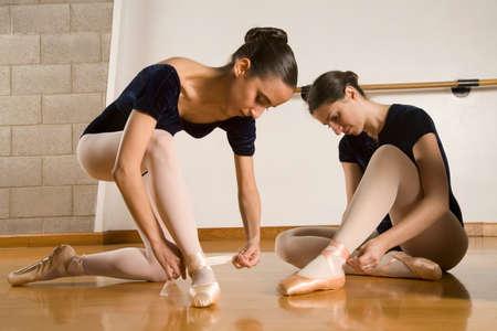 merry dancers: Hispanic female ballet dancers fastening shoes LANG_EVOIMAGES