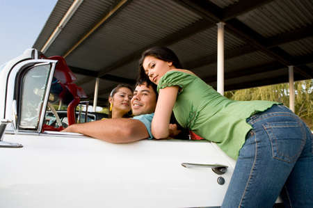 outmoded: Hispanic man with two women in convertible