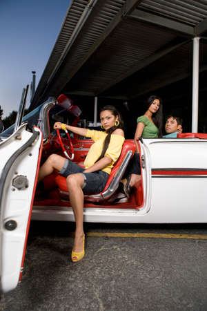 seducer: Hispanic woman sitting in convertible LANG_EVOIMAGES