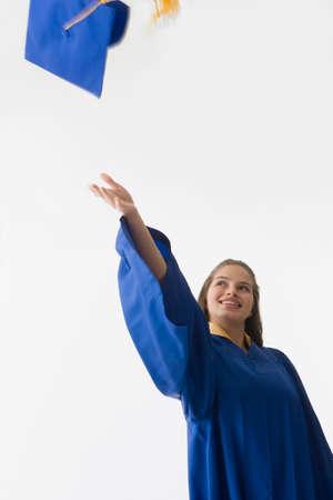 girl in full growth: Hispanic female graduate throwing cap LANG_EVOIMAGES