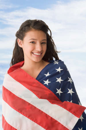 naturalization: Hispanic teenaged girl wrapped in American flag LANG_EVOIMAGES