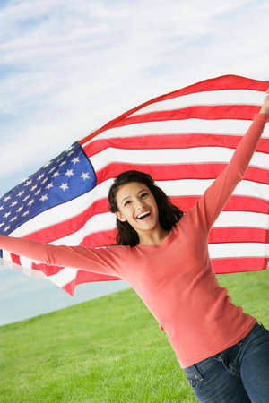 teenaged girl: Hispanic teenaged girl holding American flag