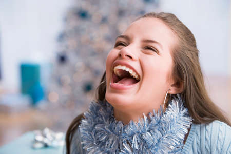 teenaged girl: Hispanic teenaged girl wearing Christmas garland LANG_EVOIMAGES