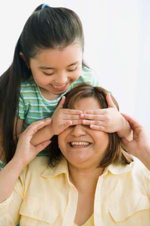 motioning: Hispanic girl covering mother's eyes LANG_EVOIMAGES