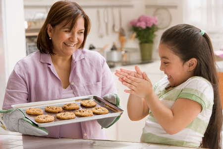 playing on divan: Hispanic madre e hija con bandeja de galletas