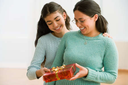 giver: Hispanic mother and daughter exchanging gift