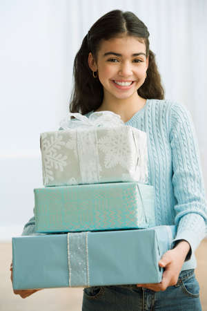dubious: Hispanic girl carrying stack of gifts